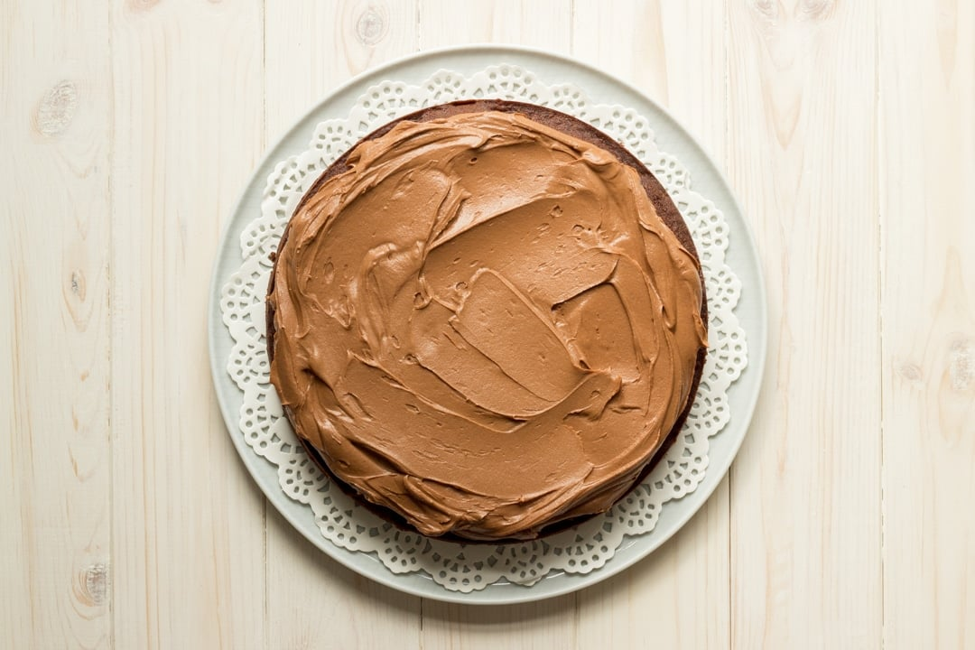 Easy chocolate cake recipe: One layer of chocolate cake on a plate topped with frosting