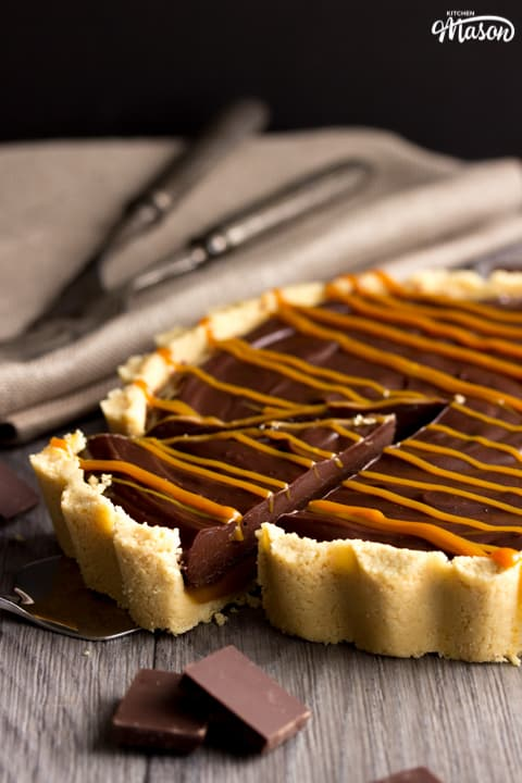 No Bake Caramel Chocolate Tart Recipe: No bake caramel chocolate tart on a worktop with a piece on a cake slice