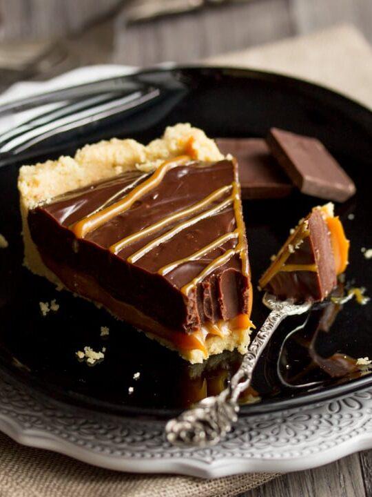 No Bake Caramel Chocolate Tart Recipe: A slice of no bake caramel chocolate tart on a plate with a fork