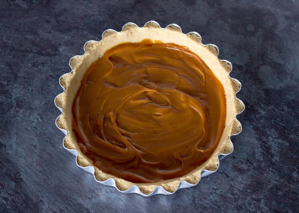 No Bake Caramel Chocolate Tart Recipe: caramel spread out in the bottom of a biscuit base in a fluted tart tin