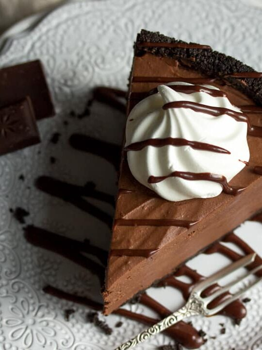 A slice of No Bake Chocolate Cheesecake on a plate topped with a meringue nest and chocolate sauce