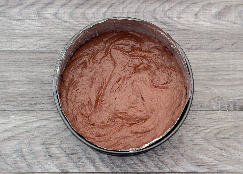 Brownie batter in a lined round cake tin