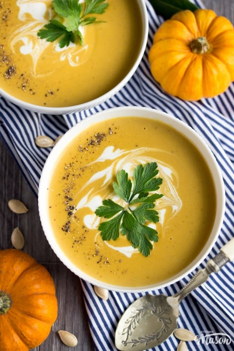 two bowls of slow cooker pumpkin soup topped with cream and parsley