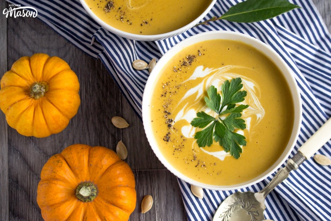 a bowl of slow cooker pumpkin soup with munchkin pumpkins in the background