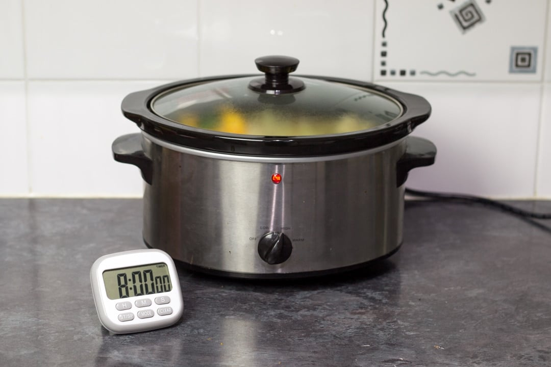 a slow cooker switched on with a timer next to it