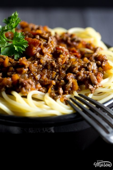 Easy spaghetti bolognese in a black bowl with a fork, topped with parsley