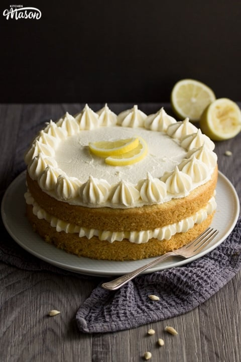 dairy free / vegan lemon cake on a plate with a fork and squeezed lemons