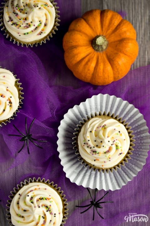 halloween cupcakes on purple tuille with a pumpkin and fake spiders