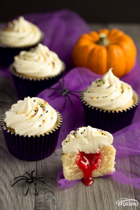 halloween cupcakes cut in half revealing a surprise blood filling with purple tuille and a pumpkin in the background
