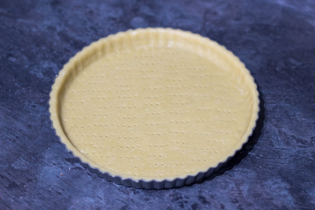 A shortcrust pastry lined tart tin with fork pricks all over the base