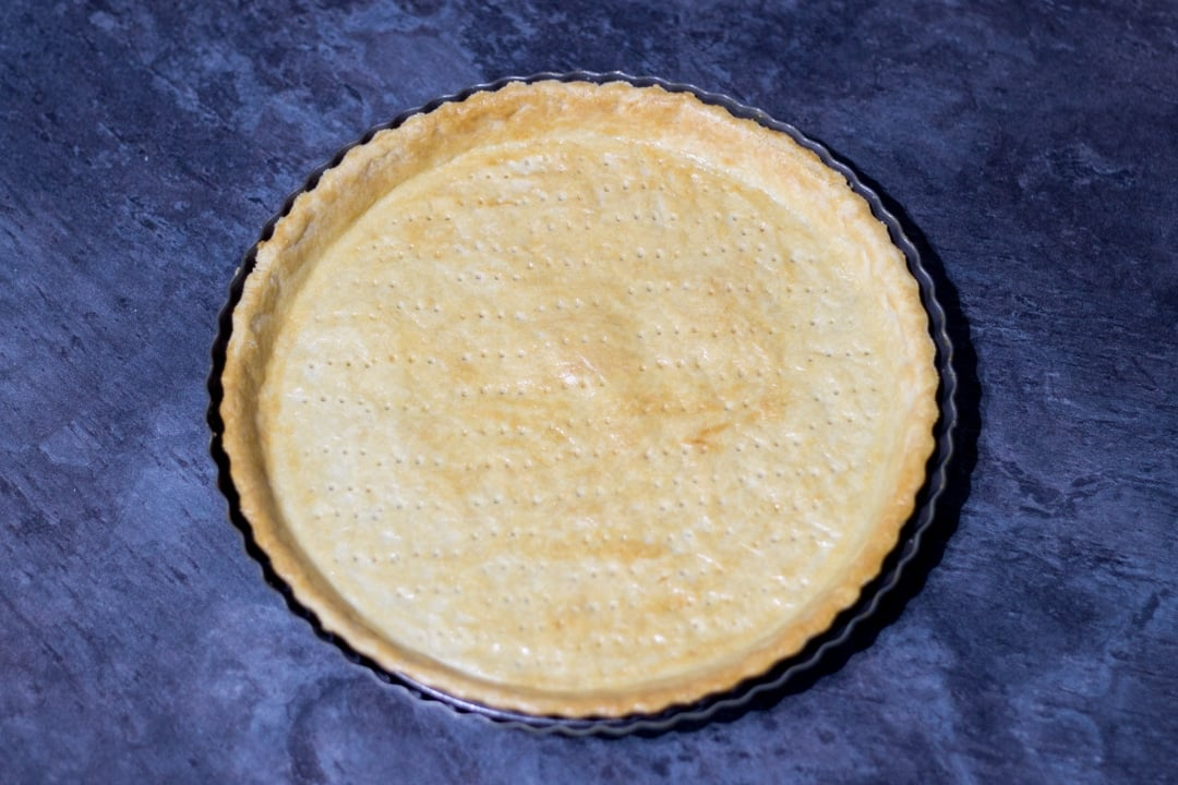 baked golden shortcrust pastry case in a tart tin