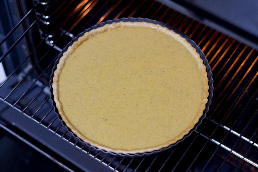 uncooked pumpkin pie on an oven shelf
