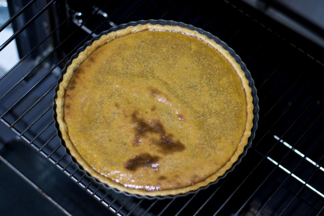 a baked pumpkin pie on an oven shelf