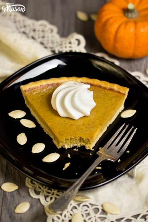 a slice of pumpkin pie with a meringue swirl on top on a black plate with a fork and pumpkin seeds