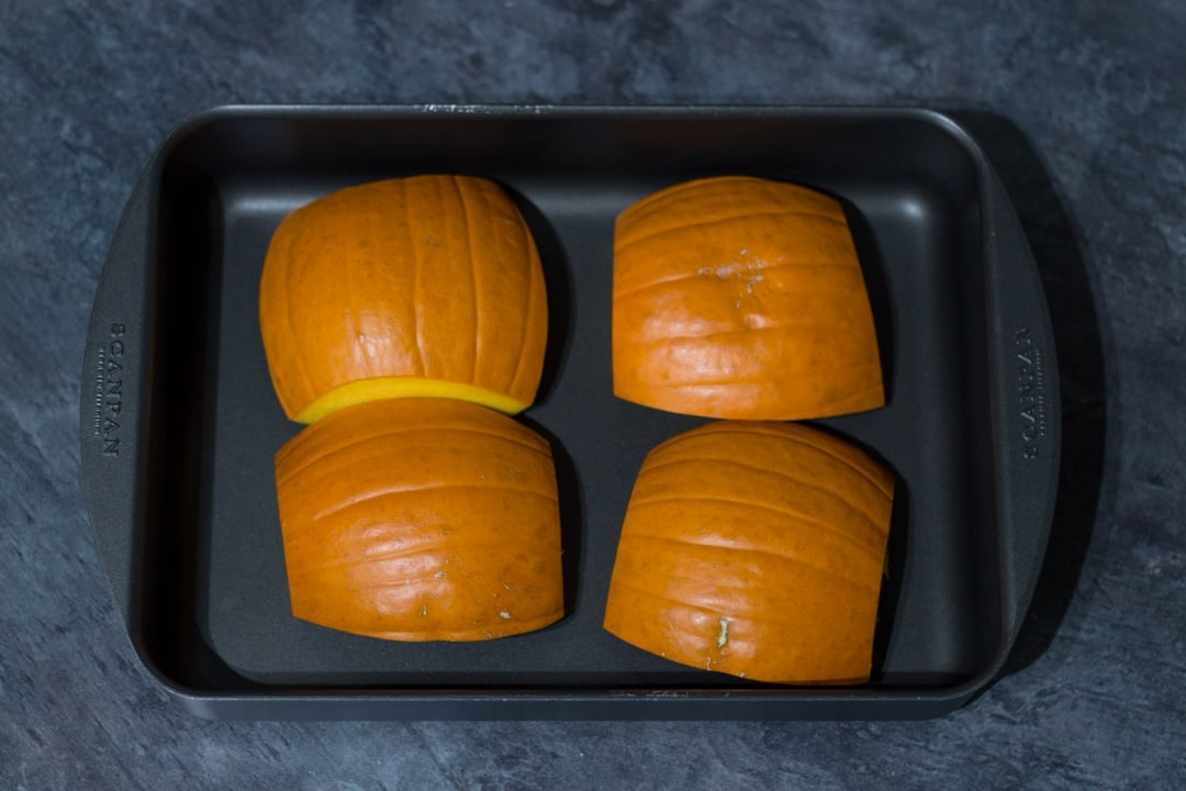 pumpkin quarters in a roasting pan