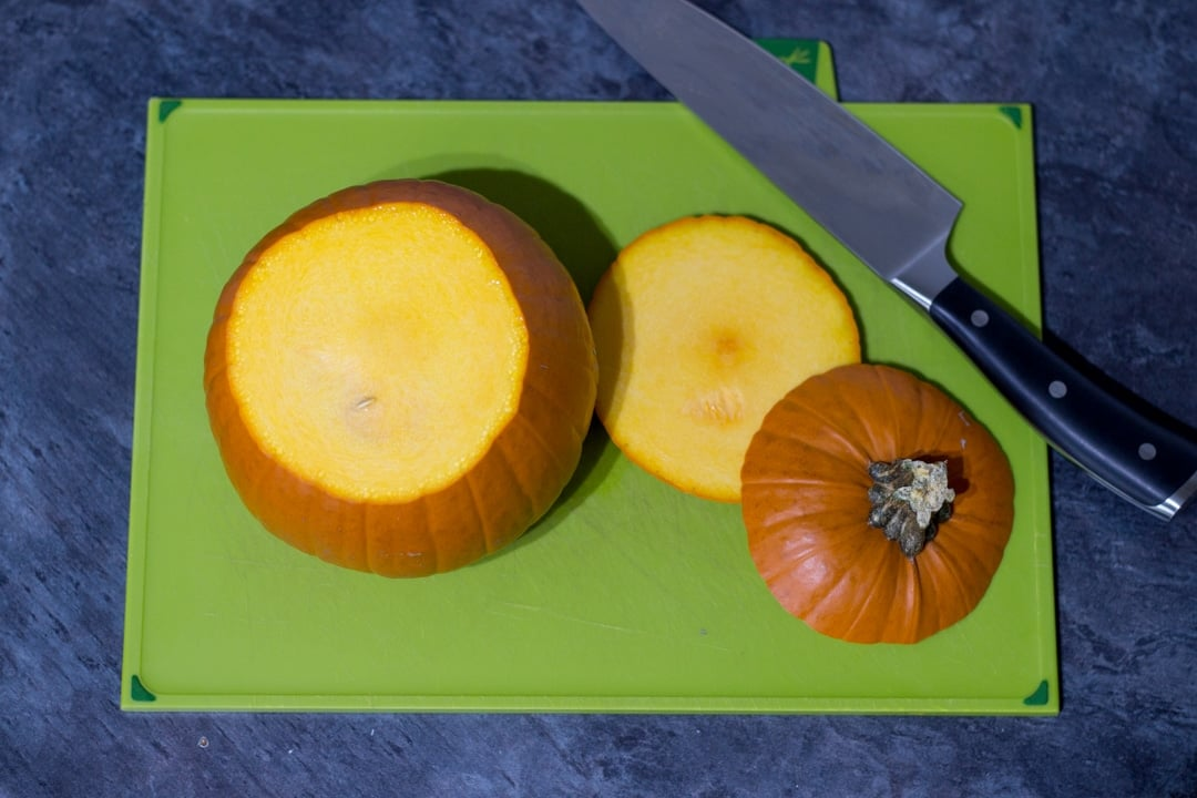 a pumpkin on a chopping board with the top and bottom sliced off