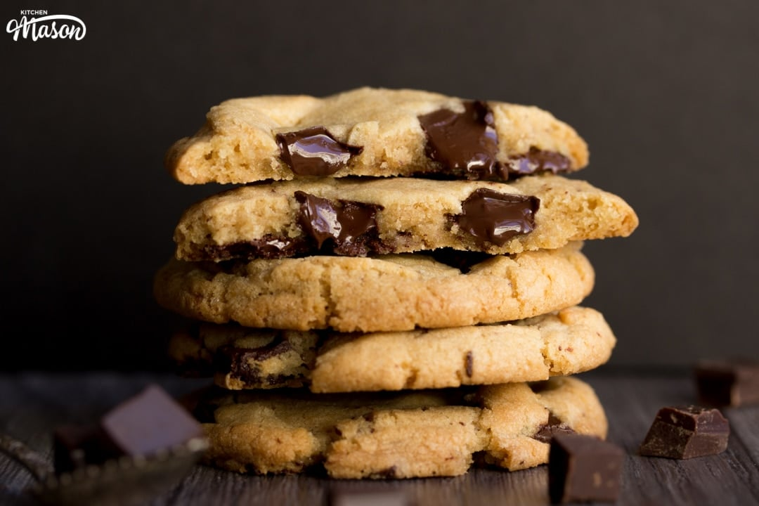 vegan chocolate chip cookies broken in half with melting chocolate chips in a stack