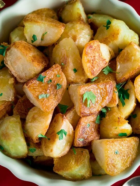 golden crispy roast potatoes in a dish scattered with parsley