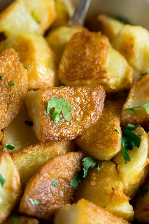crispy roast potatoes with parsley scattered on top