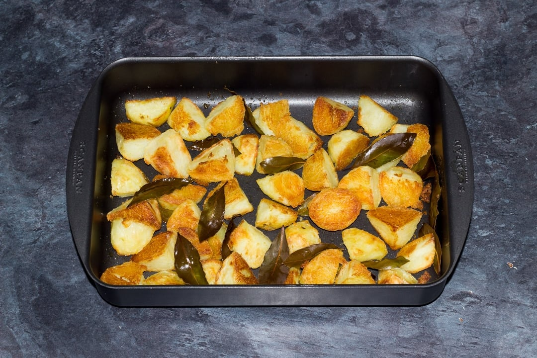 golden crispy roast potatoes in a roasting dish with bay leaves