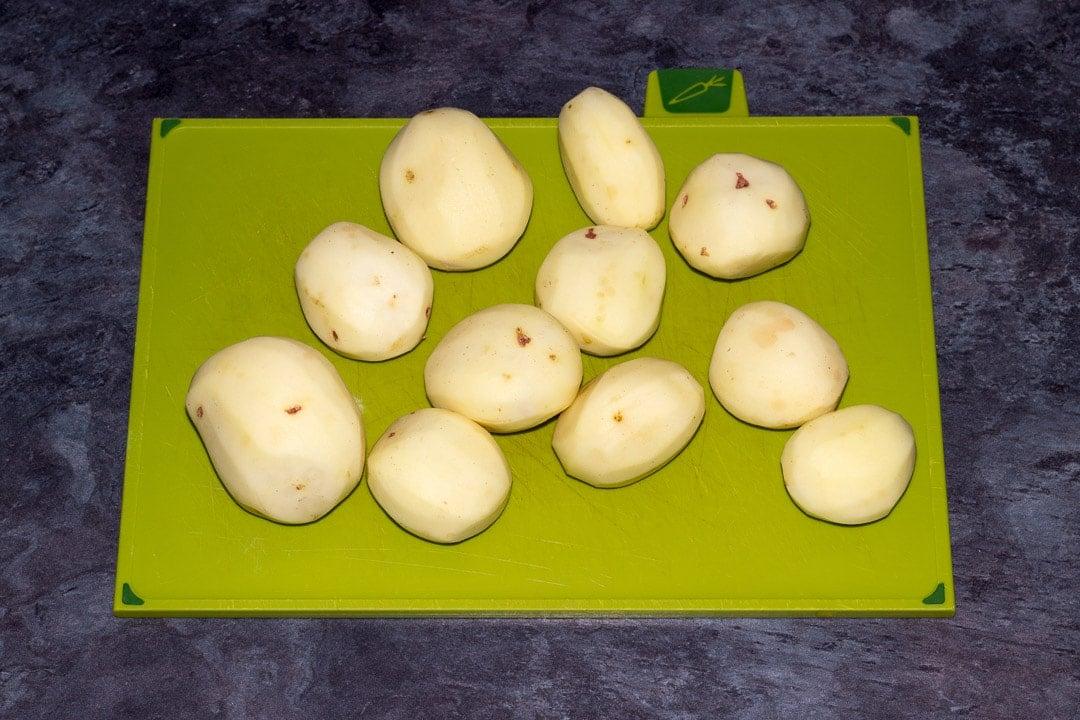 peeled potatoes on a chopping board