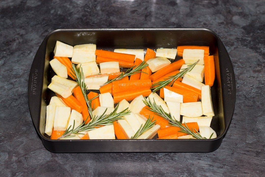 carrots, parsnips and rosemary in a roasting dish