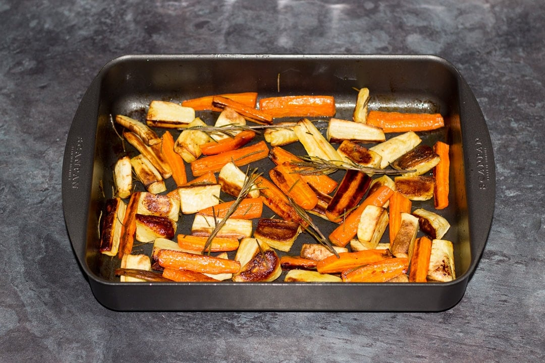 Honey roast parsnips and carrots with rosemary in a roasting tray