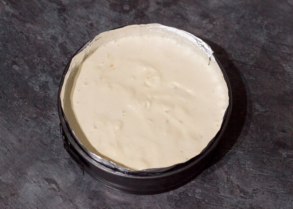 melted ice cream on top of baked brownie in a round cake tin