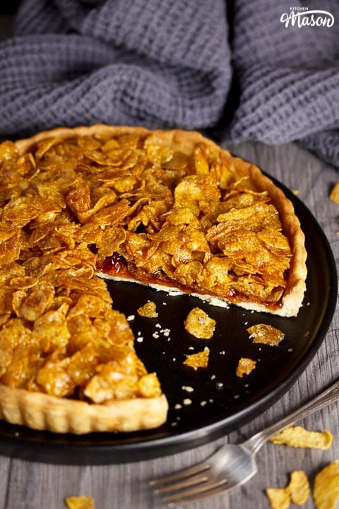 a cornflake tart with a missing slice on a black plate with crumbs around it