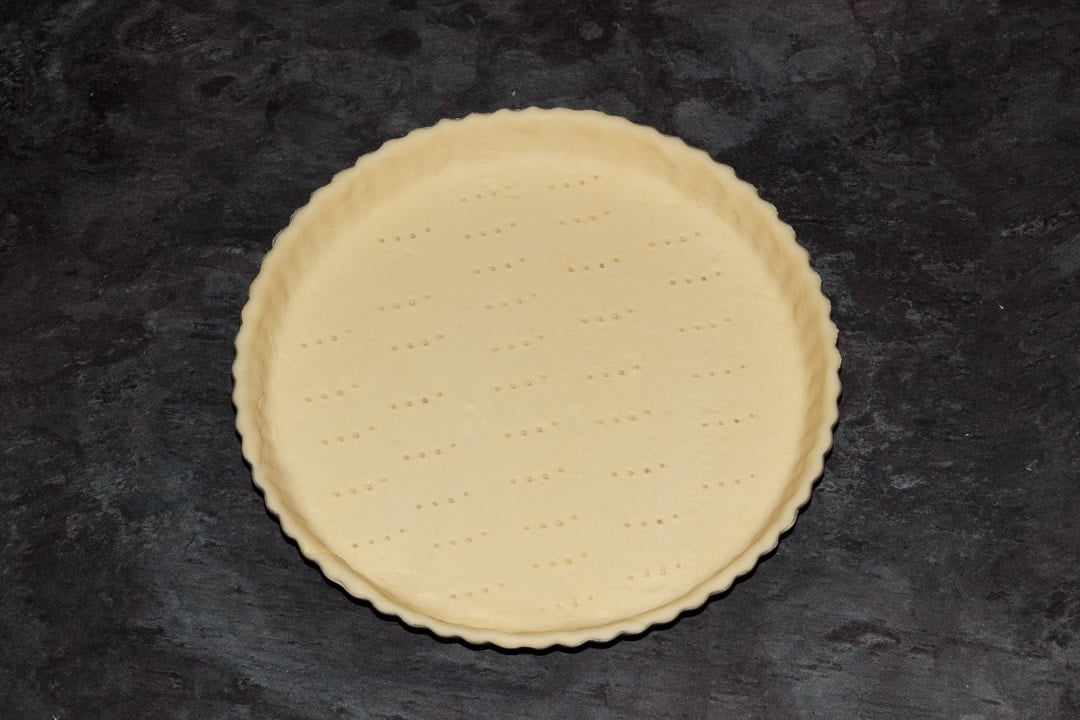 a fluted tart tin lined with shortcrust pastry