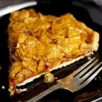 Slice of cornflake tart on a black plate with a fork