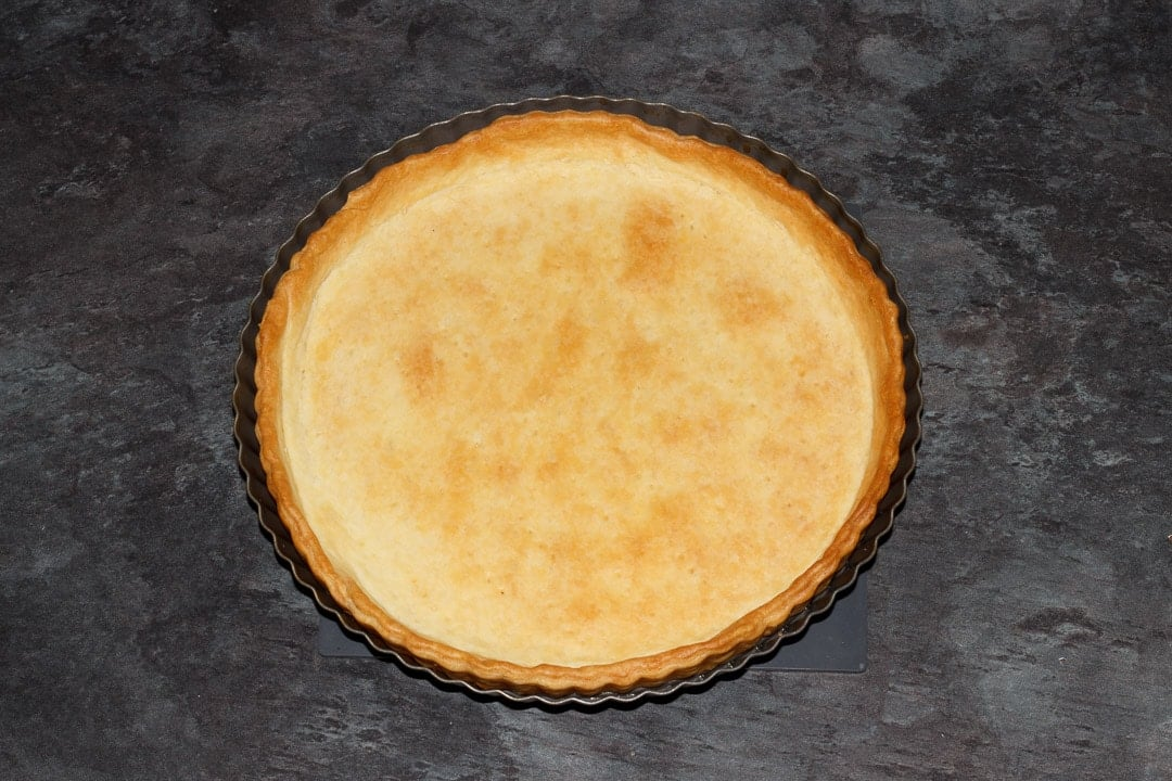 a baked shortcrust pastry case in a fluted tart tin