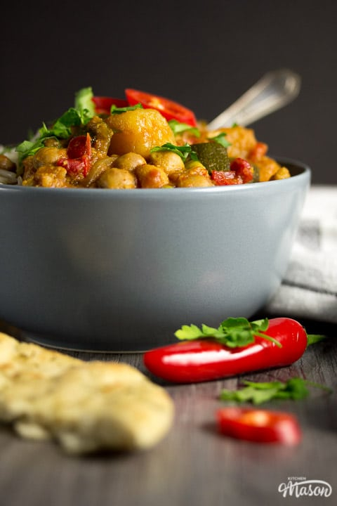 Slow cooker vegetable curry in a slow cooker in a bowl with rice, fresh coriander and fresh red chilli