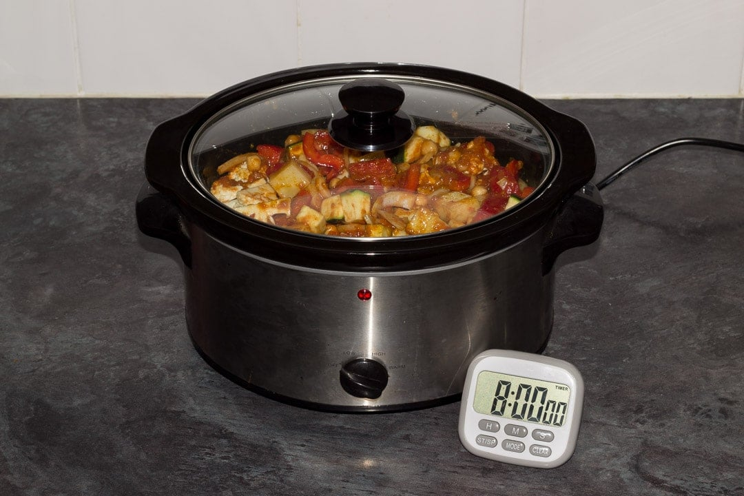 uncooked slow cooker vegetable curry with the lid on and a timer set for 8 hours