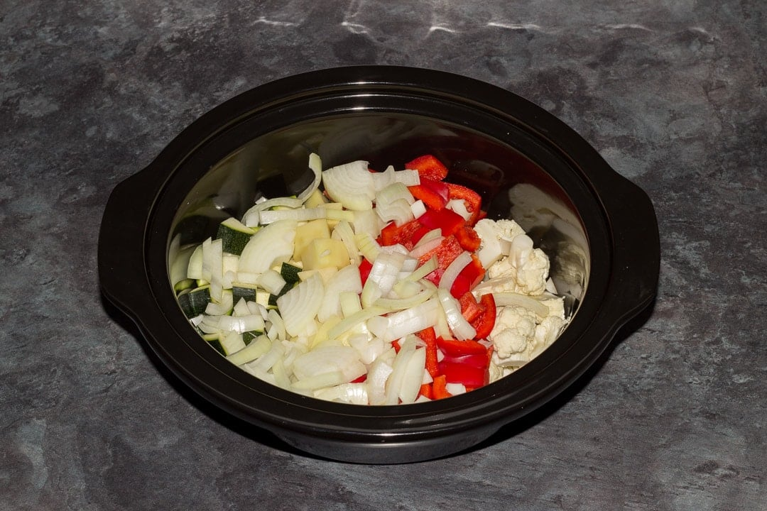 cauliflower, red pepper, onion, courgette and potato in a slow cooker bowl