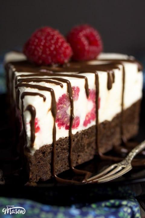 Slice of vegan gluten free raspberry brownie ice cream cake on a black plate drizzle with chocolate sauce and fresh raspberries