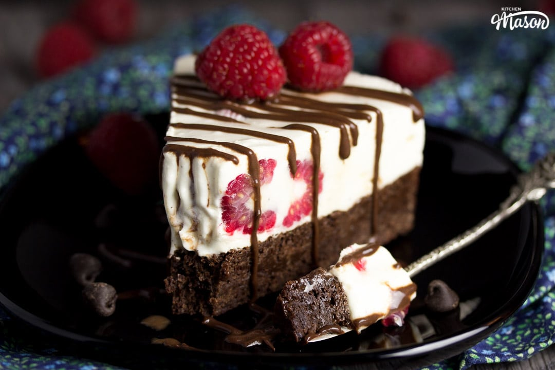 Slice of vegan gluten free raspberry brownie ice cream cake on a black plate drizzle with chocolate sauce and fresh raspberries