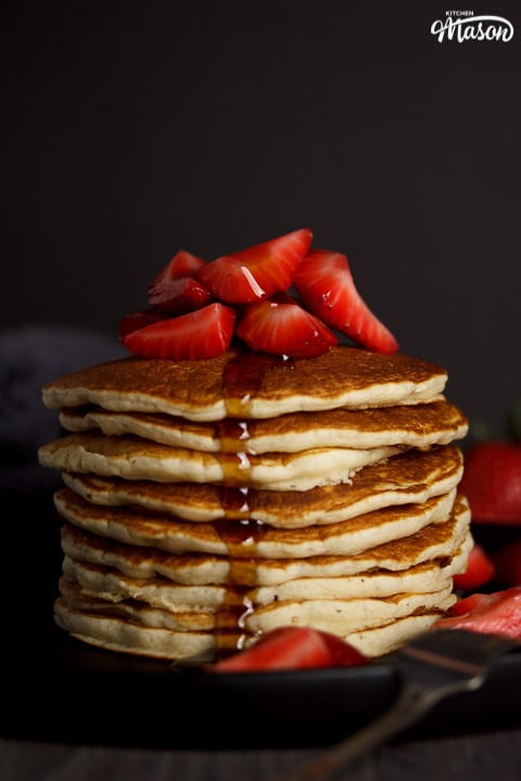 Vegan pancakes in a stack topped with strawberries, drizzled with maple syrup