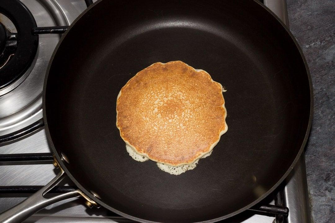 golden vegan pancake in a frying pan