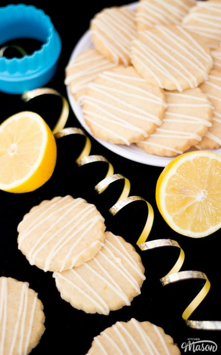 Lemon biscuits on a plate with a fluted cookie cutter and gold curling ribbon