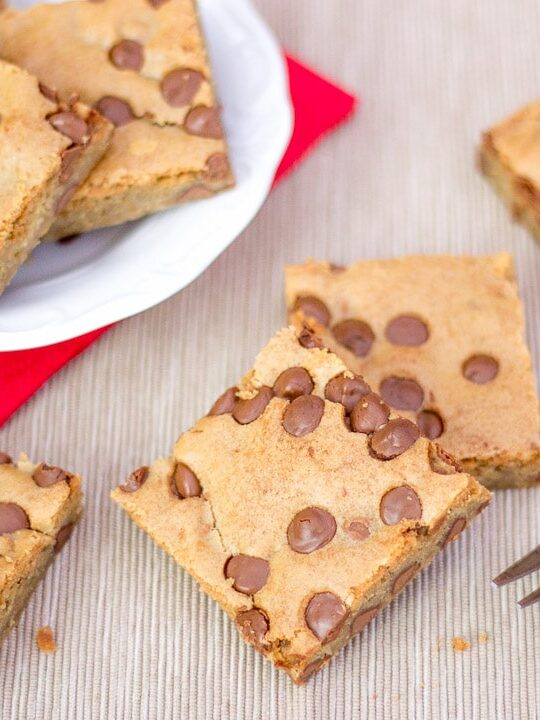 chocolate chip cookie bars on a plate and the work top with a fork
