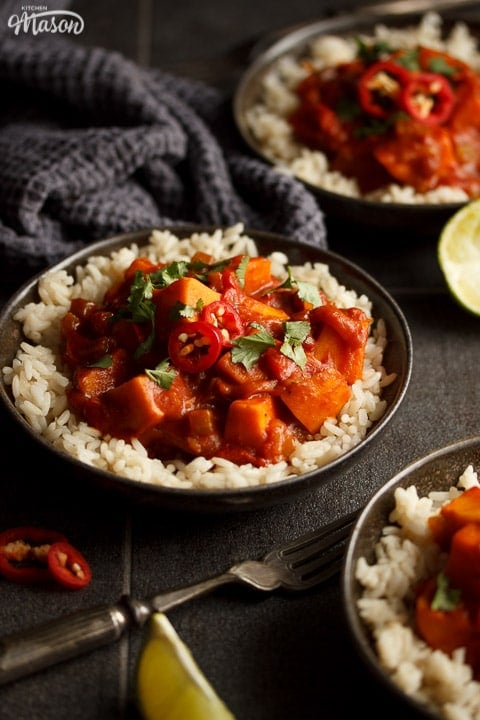 3 bowls of sweet potato curry and rice with fresh limes, forks and a dark grey tea towel