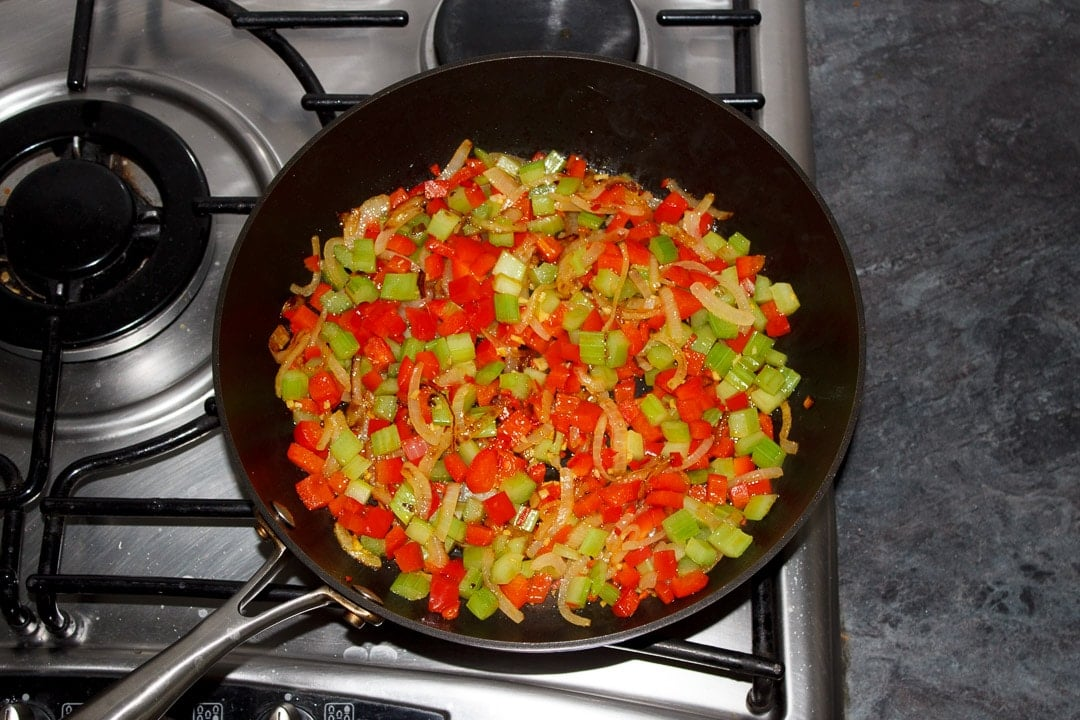 onion, red pepper, celery, ginger and chilli frying in a frying pan