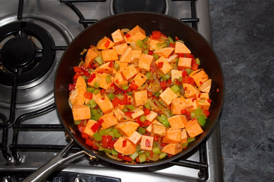 Sweet potato, onion, red pepper, celery, ginger and chilli frying in a frying pan