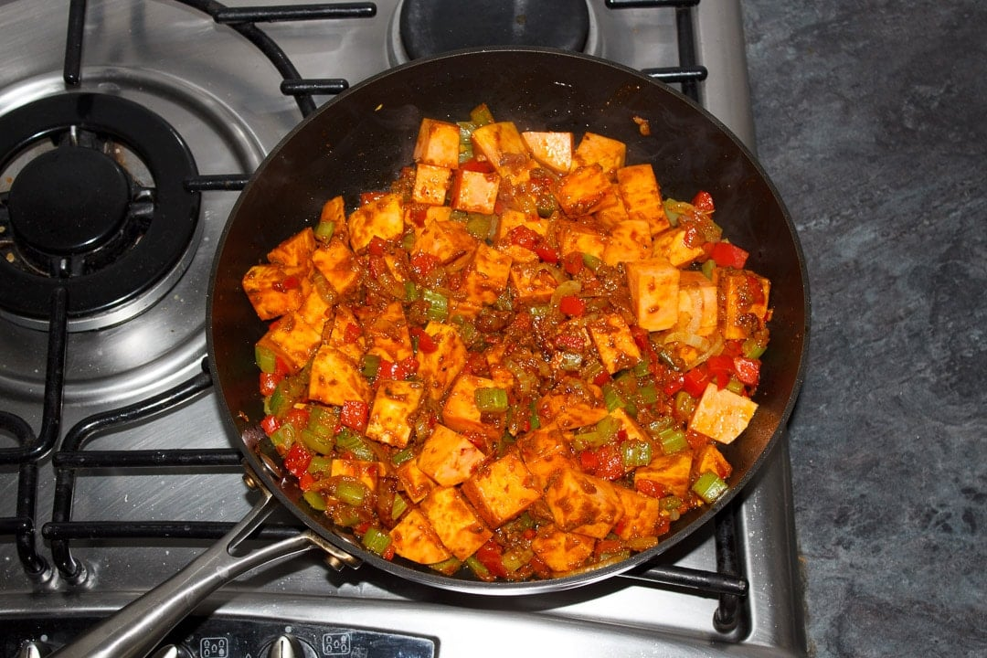 Sweet potato and other vegetables frying in a frying pan covered in curry paste