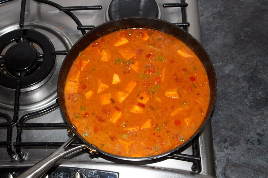 Sweet potato curry simmering in a frying pan