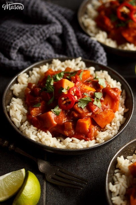 A bowl of sweet potato curry and rice with fresh limes, a fork and a dark grey tea towel