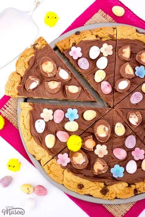 Easter Chocolate Cookie Pizza sliced up on pink fabric with little yellow chicks
