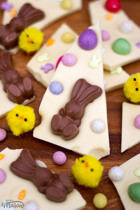 White Chocolate Easter Bark broken up on a chopping board with little yellow chicks