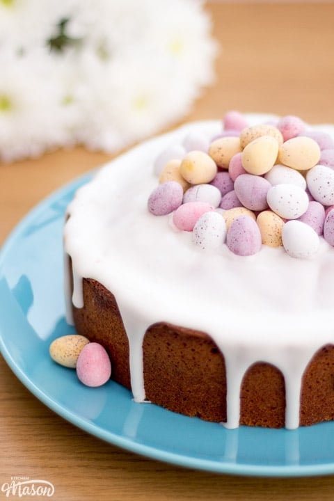 Lemon Drizzle Easter Cake on a blue plate topped with mini eggs